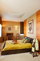 Low bed with shiny, yellow bedspread against wood-clad wall; chair and table below sconce lamps on wall in background