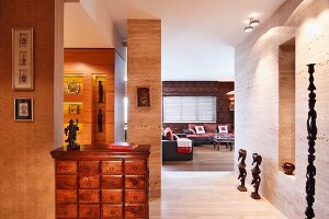 Apothecary cabinet in hallway, ethnic sculptures on floor against wall and view into lounge area in background