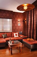 Rust red sofa set and ethnic coffee table in lounge with patterned wallpaper, matching curtain and pendant lamp with metal lampshade