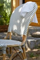 A designer rattan chair with grey and white plastic wickerwork