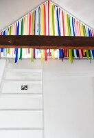White ladder leading to gallery in attic with colourful ribbon curtain screening entrance