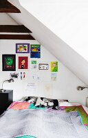 Bedroom with sloping ceiling, double bed with bedspread, retro bedside lamp and children's drawings