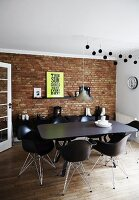 Unrendered brick wall in dining area with wooden floor and designer furniture