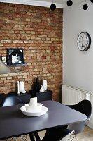 Station clock, unrendered brick wall, black designer furniture and white vases in dining room