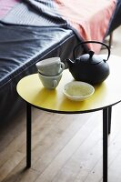 Cast iron teapot and teacups on yellow, kidney-shaped side table in front of black leather sofa