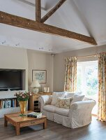Seating area in front of fireplace with country-house kitchen, pale wooden furniture and floral curtains; exposed roof beams