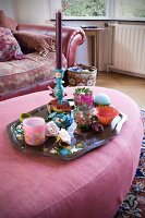 Collection of tealight holders and candle lanterns on tray on pink ottoman