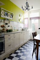 Kitchen counter with white cupboards against wall painted green with tiled splashback; chequered floor tiles