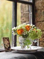 Posy of ranunculus and viburnum in glass vase on windowsill
