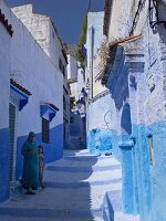 A woman and a little girl in one of the blue alleys in the Medina of Chefchaouen, Morocco