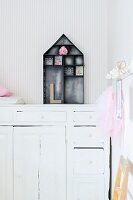 House-shaped, dark metal display case on top of white, vintage cabinet