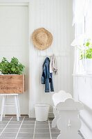 White-painted wooden bench, straw hat on coat peg and potted plant in vintage wooden crate