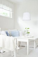 Seating area in white, Scandinavian interior with sofa and table with folding side leaves