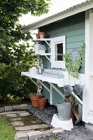 Gardening utensils on table and shelves below eaves of Swedish garden shed