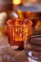 Orange tealight holder on Christmas table (close-up)