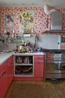 Eclectic kitchen with floral wall, Spanish posters and pink-painted cabinets