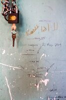 Padlock next to hand-drawn height scale on battered wall