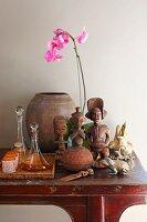 Folkloristische Figuren aus Holz neben Tablett mit Glaskaraffen und Becher, pinkfarbene Orchidee, auf Wandtisch