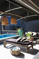 Rustikale Holzbänke mit Liegepolstern, auf sonniger Terrasse unter Sonnenschutz aus dunklem Stoff, im Hintergrund Pool