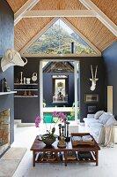 Niedriger Holztisch in offenem Wohnraum, im Hintergrund helles Polstersofa vor schwarz getönten Wänden, sichtbarer Dachstuhl mit Bambusabdeckung