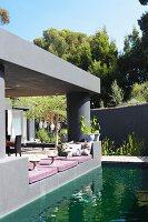 Angelegter Teich vor modernem Wohnhaus mit überdachter Terrasse, grau getönt, gemütliche Sitzpolster an Terrassenrand