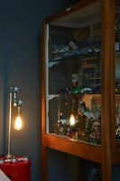 Table lamp next to retro toys in glass-fronted cabinet