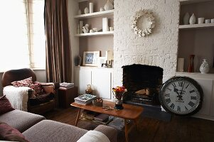 Corner of living room - sofa and armchair around fifties coffee table in front of open fireplace flanked by vases on fitted shelving in niches and antique station clock on floor
