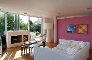 White sofa bed, set of coffee tables and open fireplace in living room with pink wall
