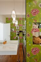 Sink on mirrored wall and floor-mounted taps in designer bathroom with floral wallpaper