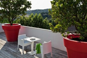 Terrace with modern, white outdoor furniture and large, red planters