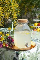 Home-made lemonade in vintage jar on tray next to colourful bouquet of wildflowers