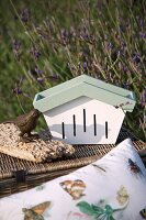 Butterfly box, bird ornament and picnic basket outdoors