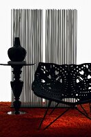 Plastic shell chair with perforated floral pattern and vase on pedestal tale on orange, long-pile rug