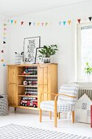 Armchair with diamond pattern and toys in rustic wooden cabinet below colourful bunting