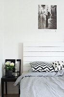 Black and white patterned scatter cushions on bed with white, wooden headboard next to black chair used as bedside table