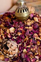 Dried rose petals with an incense burner
