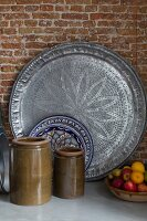Ceramic pots with olive-green glaze, plate with ethnic pattern and large, pewter platter in front of brick wall