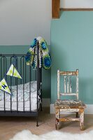 Wooden chair with peeling paint and cot with dark frame, bunting and crocheted blanket