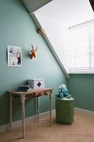 Stylised hunting trophy above old console table with peeling paint and soft toy on top of basket