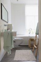 Modern bathroom with designer bathtub below window; stool and ladder-style towel rack made from plain wood