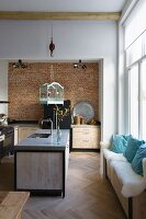 Vintage bird cage hung from load hook above island counter in modern, loft-apartment kitchen with window seat