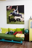 DIY sofa made from pallets below large picture on wall