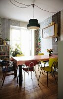 Colourful retro chairs at dining table with tablecloth below pendant lamp