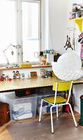 Vintage chair at desk below window; paper lampshade partially covered in paper cups