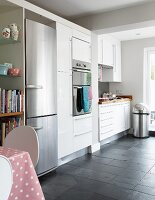 Contemporary kitchen with white fitted cupboards and integrated stainless steel fridge
