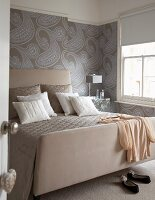 Double bed with upholstered headboard against wall with paisley wallpaper in bedroom in various shade of grey