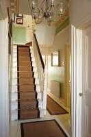 Staircase with runner and traditional hallway in English house