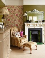 Armchair with footstool against floral wallpaper and open fireplace with shelves integrated into surround in traditional living room