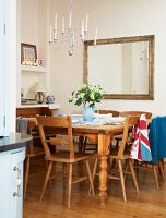 Rustic wooden dining set below multi-armed candle chandelier