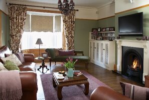 Traditional living room with leather sofa set in front of fireplace, opium table and antique chaise in window bay